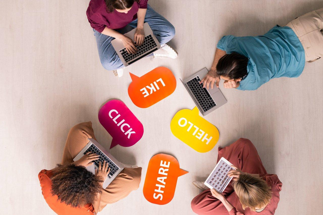 Above view of young people sitting and lying on floor with internet activity tags and using modern portable devices
